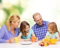 与两个孩子的愉快的家庭与食用早餐 库存图片