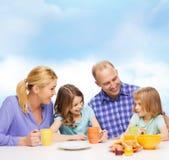与两个孩子的愉快的家庭与食用早餐 免版税库存照片