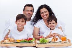 与两个孩子的愉快的家庭吃早餐在床 库存图片