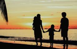 与两个孩子的愉快的家庭在日落海滩 免版税库存图片