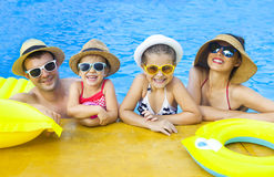 与两个孩子的愉快的家庭获得乐趣在游泳池 免版税图库摄影