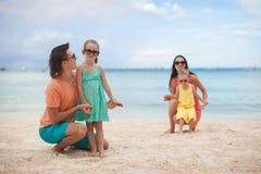 与两个孩子的年轻美丽的家庭在热带 库存图片