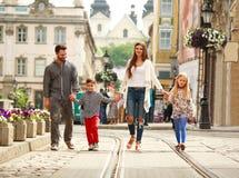 与两个孩子走的街道老旅游城市的年轻家庭 免版税库存照片