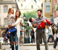 与两个孩子走的街道老旅游城市的年轻家庭 免版税图库摄影