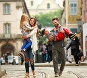与两个孩子走的街道老旅游城市的年轻家庭 库存图片