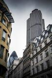 与两个摩天大楼的伦敦市大厦在喜怒无常的天空下 库存图片