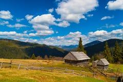 与两个木房子的山风景 库存图片