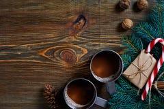 与两个杯子的圣诞节礼物热奶咖啡、坚果、锥体和冷杉分支在木背景关闭 库存照片