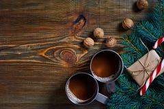 与两个杯子的圣诞节礼物热奶咖啡、坚果、锥体和冷杉分支在木背景关闭 免版税库存图片