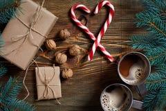 与两个杯子的圣诞节礼物热奶咖啡、坚果、锥体和冷杉分支在木背景关闭 库存图片