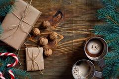 与两个杯子的圣诞节礼物热奶咖啡、坚果、锥体和冷杉分支在木背景关闭 图库摄影