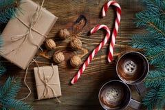 与两个杯子的圣诞节礼物热奶咖啡、坚果、锥体和冷杉分支在木背景关闭 免版税库存照片
