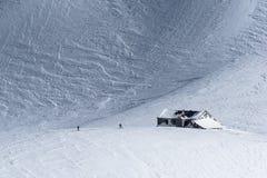 与两个滑雪者的积雪的高山山小屋在冬天 免版税库存图片