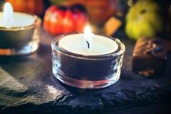 与两个烛光、巧克力和南瓜的万圣夜装饰在板岩 免版税图库摄影