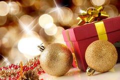 与两个球和礼物对角com的金黄圣诞节装饰 库存照片
