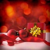 与两个球的红色圣诞节装饰和礼物丝带摆正 免版税库存图片