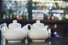 与两个白色茶壶的酒吧柜台 免版税库存图片