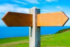 与两个箭头的空白的木路标在与拷贝空间的清楚的蓝天 库存照片