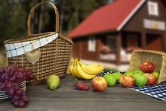 与两个篮子的野餐桌和果子临近乡间别墅 库存照片