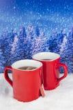 与两个红色杯子的圣诞节装饰在backgroun的热的茶 免版税图库摄影