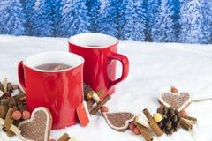 与两个红色杯子的圣诞节装饰在backgroun的热的茶 免版税库存图片