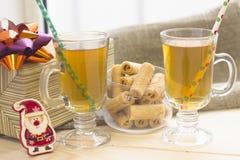 与两个茶杯、一碗曲奇饼,礼物盒和玩具圣诞老人的一幅欢乐静物画 免版税库存图片