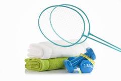 与两个蓝色健身哑铃的白色和绿色毛巾包裹与黄色测量的磁带和两副蓝色羽毛球拍 库存图片