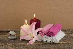 与两个蜡烛、堆温泉石头和毛巾的美好的构成在木背景 免版税库存照片