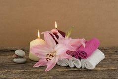 与两个蜡烛、堆温泉石头,桃红色百合和毛巾的美好的构成在木背景 免版税库存图片