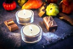 与两个蜡烛、巧克力和南瓜的万圣夜装饰 库存图片