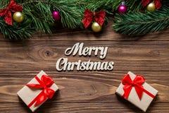 与两个豪华礼物盒的逗人喜爱的圣诞快乐题材在木背景 免版税库存图片
