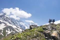 与两个远足者的山风景高小山看看峰顶的多雪的山在清楚的晴朗的夏日 登上的登山人远足 免版税库存图片