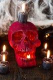 与两个长的红色蜡烛的红色天鹅绒蜡烛台围拢的一块红色天鹅绒头骨几乎烧光 驱散在头骨附近 免版税图库摄影