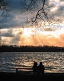 与两人的日落场面一条长凳的在冬天 免版税库存图片
