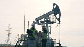 与两位燃料工程师的抽油井架有讨论在它附近 运转的油泵,在背景的抽油装置 股票录像