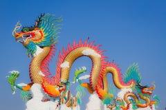 与两只小鸟的中国龙雕象在它的后面 图库摄影