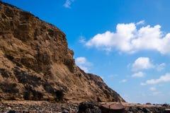 与两只海鸥的坚固性接合的棕色峭壁边缘 与残破的松的云彩的深刻的天空蔚蓝背景 图库摄影