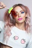 与两吃五颜六色的棒棒糖的桃红色马尾辫发型的秀丽模型 免版税图库摄影