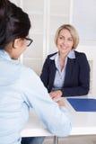 与两名女实业家的采访书桌的在办公室。 库存图片