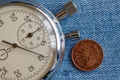 与两在蓝色牛仔布背景-企业背景的欧分(后部)和秒表的衡量单位的欧洲硬币 免版税库存照片