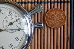 与两块欧分和秒表的衡量单位的欧洲硬币在木桌-后部上 库存照片