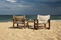 与两张椅子和桌的海边视图与对此的一块空的玻璃 免版税库存照片