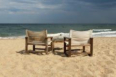 与两张椅子和桌的海边视图 免版税库存图片