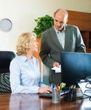 与两成熟和严肃的工作者的办公室场面 免版税图库摄影