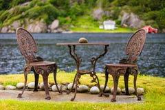 与两把椅子室外近的湖的咖啡桌 免版税库存图片