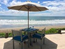与两把椅子的表临近海 免版税库存图片