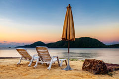 与两把老椅子的日落热带海滩 库存图片