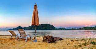 与两把老椅子的日落热带海滩 免版税图库摄影