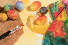 与两把画家刷子和一块手画布料的复活节五颜六色的鸡蛋,安排在与黄色的水彩纸绘了文本 免版税库存图片