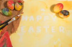 与两把画家刷子和一块手画布料的复活节五颜六色的鸡蛋,安排在与黄色的水彩纸绘了文本 图库摄影